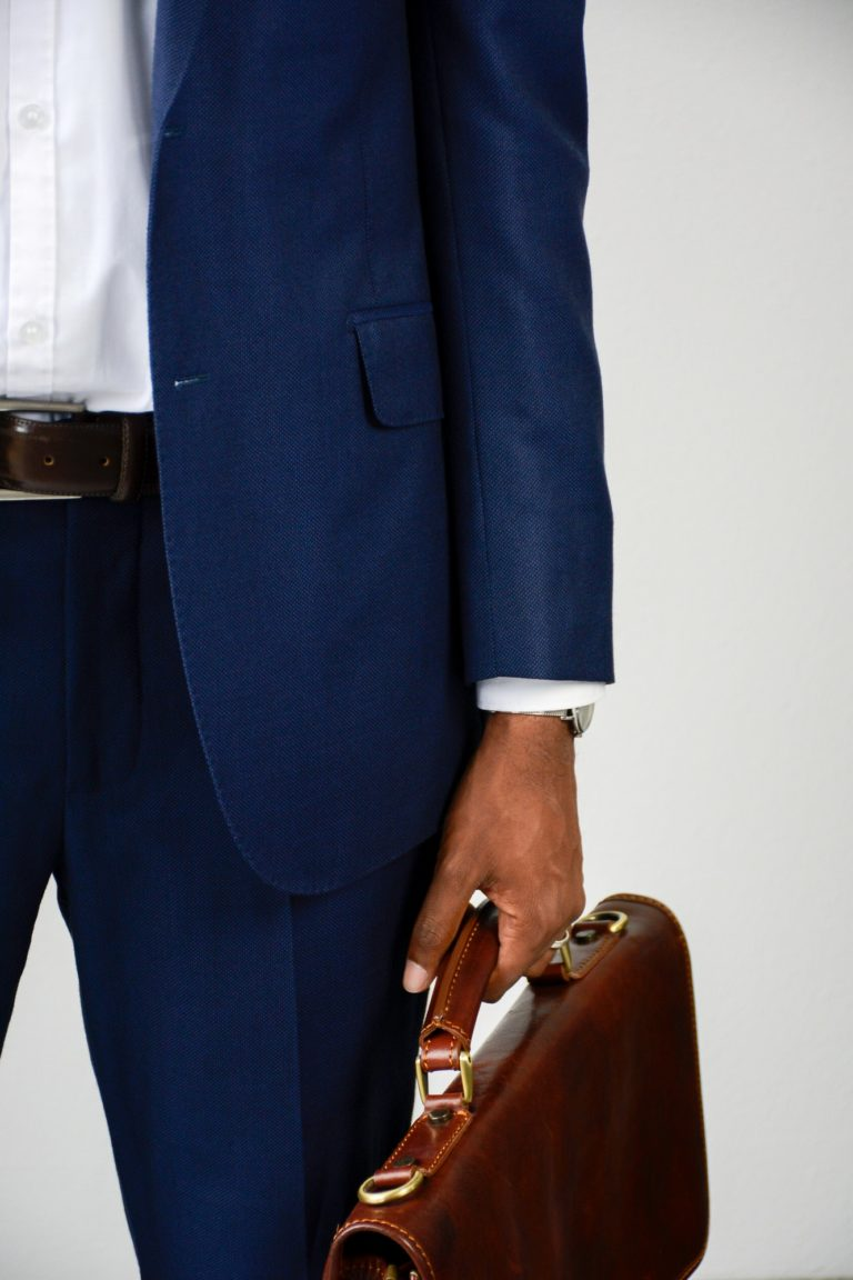 Close up of stylish young businessman in blue formal wear holding briefcase. Man in business suit.